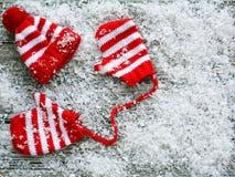 Schnee bedeckte kleinen roten und weißen abgestreiften Hut mit Handschuhen lizenzfreies stockbild