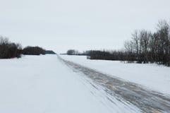 Schnee bedeckte Landstraße in Saskatchewan Stockbilder
