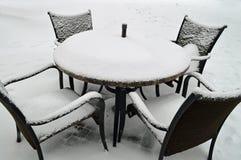Schnee bedeckte Patiomöbel im Freien Stockfotografie