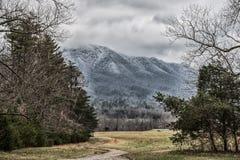 Schnee bedeckte rauchige Berge an einem kalten Wintertag mit einer Kappe stockfotografie