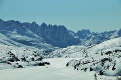 Schnee bedeckte Sägezahnberge und gefrorenen See im Britisch-Columbia stockfotos