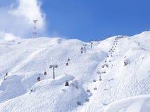 Schnee bedeckte Steigungen mit roten Drahtseilbahnen und Sesselbahnen mit freien Fahrten und Pistes im Gebirgsskiort Kaprun stockfotos