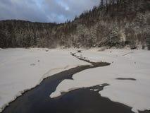 Schnee bedeckte teils gefrorenen Waldteich oder -see mit Wasserstromnebenfluß mit geziertem Baumwald, idyllische Winterlandschaft lizenzfreies stockbild