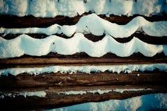 Schnee bedeckter hölzerner Stapel stockfotos