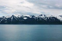 Schnee-Berge mit Ozean in Island Lizenzfreie Stockbilder