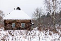 Schnee deckte hölzernes rustikales Haus ab Stockbilder
