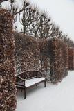 Schnee deckte Parkbank ab Stockfoto