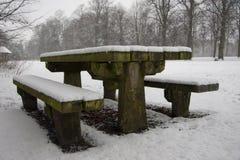 Schnee deckte Picknickbank ab Stockfotos