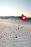 Schnee deckte windige rote Fahne des Link-Golfplatzes ab Stockfoto