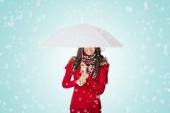 Schnee, der auf Frau unter Regenschirm fällt Stockbild