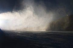 Schnee, der auf Steigung macht Skifahrer nahe einer Schneekanone, die frischen Pulverschnee macht Gebirgsskiort in der Winterruhe Lizenzfreie Stockfotografie