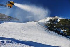 Schnee, der auf Steigung macht Skifahrer nahe einer Schneekanone, die frischen Pulverschnee macht Gebirgsskiort in der Winterruhe Stockfotografie