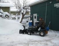 Schnee, der auf Traktor durchbrennt Stockbilder