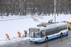 Schnee, der durch Leute von den öffentlichen Einrichtungen in Moskau entlang der Landstraße sich klärt und Bus führt stockbilder