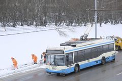 Schnee, der durch Leute von den öffentlichen Einrichtungen in Moskau entlang der Landstraße sich klärt und Bus führt stockfoto