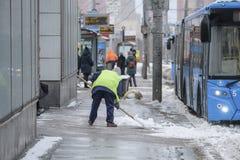 Schnee, der durch Leute von den öffentlichen Einrichtungen in Moskau nahe der Bushaltestelle sich klärt stockfoto