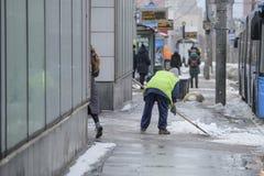 Schnee, der durch Leute von den öffentlichen Einrichtungen in Moskau nahe der Bushaltestelle sich klärt stockfotos