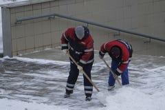 Schnee, der durch Leute von den öffentlichen Einrichtungen in Moskau nahe der Unterführung sich klärt lizenzfreie stockfotos