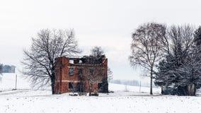 Schnee, der einen verlassenen Bauernhof bedeckt Stockfotografie