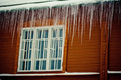 Schnee, Eiszapfen und Eis-Verdammung auf Dach- und Gossenfenster stockfotografie