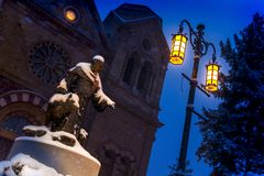 Schnee-Fälle schwer auf diese Nachtzeitszene der Basilika von St Francis und von St Francis von Assisi-Statue in Santa Fe New Mex lizenzfreie stockbilder