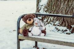 Schnee fällt auf die Spielwaren, die auf der Bank sitzen Stockbilder