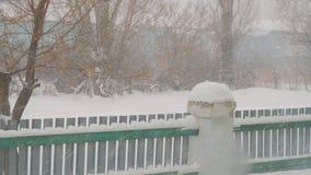 Schnee f?llt auf den Hintergrund des kleinen Zauns stock video