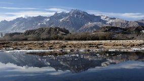 Schnee-Gebirgsreflex auf Wasser. lizenzfreies stockbild