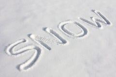 SCHNEE geschrieben auf einem Snowy-Gebiet Stockfotos
