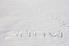 SCHNEE geschrieben auf einem Snowy-Gebiet neben Abdrücken Stockfotos