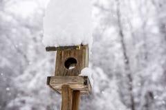 Schnee häufte Hoch auf einem hölzernen Vogelkasten an Lizenzfreie Stockbilder