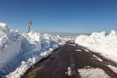 Schnee h?ufte hoch neben einer Heidemoorstra?e nach einem Blizzard an stockfoto