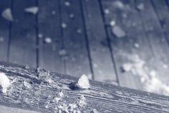 Schnee im Frühjahr auf einer hölzernen Plattform Lizenzfreie Stockfotografie