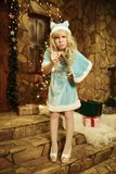 Schnee-Mädchen auf der Türstufe des Hauses verziert in der Weihnachtsart Stockfotografie