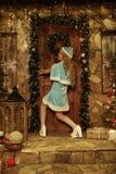 Schnee-Mädchen auf der Türstufe des Hauses verziert im Weihnachtsartversuch zur offenen Tür Stockfoto