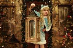 Schnee-Mädchen hält Laterne auf der Türstufe des Hauses verziert in der Weihnachtsart Stockbild