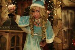 Schnee-Mädchen hält Laterne auf der Türstufe des Hauses verziert in der Weihnachtsart Lizenzfreies Stockfoto