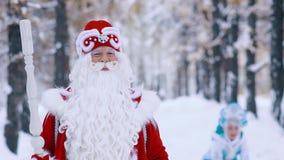 Schnee-Mädchen im Hintergrund, der den Schnee bis zur Luft, Vater Frost im Vordergrund wirft stock video footage