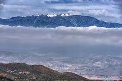 Schnee mit einer Kappe bedeckte Berge mit Wolkenbank Lizenzfreie Stockfotos