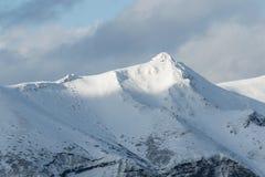 Schnee-mit einer Kappe bedeckte Berge nahe dem Meer im Winter Lizenzfreies Stockfoto