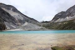 Schnee mit einer Kappe bedeckte Berge und farbiges Meer Lizenzfreie Stockfotografie