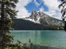Schnee mit einer Kappe bedeckte Berge und klarer See Stockfotos