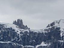 Schnee mit einer Kappe bedeckte Bergspitzen mit Sturmwolken Stockfotos