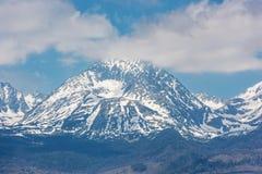 Schnee-mit einer Kappe bedeckte Spitzen von felsigen Bergen mit blauem Himmel und Wolken Stockfoto
