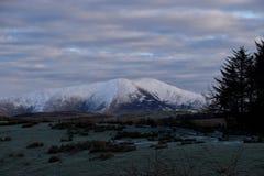 Schnee mit einer Kappe bedeckter Berg an der Dämmerung Stockfotografie