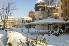 Schnee treibt auf grünen Büschen und Sommer café in der Mitte der alten Stadt des Bulgaren Pomorie Stockfotografie