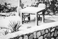 Schnee umfasste Gartentisch und Sitze Stockfotos