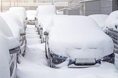 Schnee umfasste ows von Autos im Parkplatz Städtische Szene, Schneesturm Säubern Sie Automobil vom Schnee Stockfotos