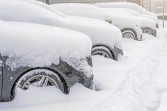 Schnee umfasste ows von Autos im Parkplatz Städtische Szene, Schneesturm Säubern Sie Automobil vom Schnee Lizenzfreie Stockbilder