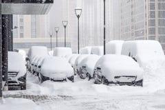 Schnee umfasste ows von Autos im Parkplatz Städtische Szene, Schneesturm Säubern Sie Automobil vom Schnee Stockfotografie
